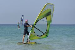 Young sports woman Windsurfing at sea on a Sunny day. royalty free stock photo