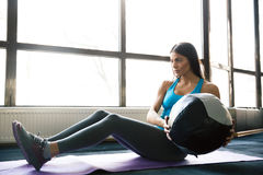 Young sports woman working out with fit ball. On yoga mat at gym Royalty Free Stock Photography