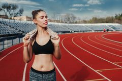 Young sports woman after workout with towel on his shoulders on the stadium after runing workout royalty free stock photo