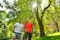 Young sports women, men enjoys driving and bright sunshine. Group of young people enjoying the driving and bright sunshine, having fun riding on a bicycle Stock Image