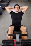 Young sportsman in black sportwear making abdominal exercises in gym. Stock Images
