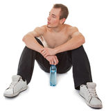 Young sportsman with a bottle of clear liquid. Young man with a bare torso holding a bottle of clear liquid Stock Photo