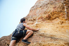 Young sportsman climbing up a rock cliff. Young handsome sportsman climbing up a rock cliff Stock Images