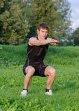 Young sportsman crouches Royalty Free Stock Photo