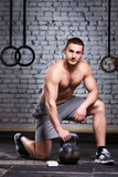 Young sportsman crouching on a one leg and holding kettlebell against brick wall in the cross fit gym. Athletic man in the shorts and sporty shoes. Vertical Royalty Free Stock Photos
