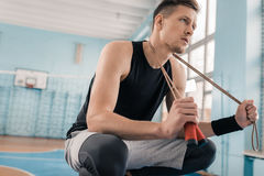 Young sportsman crouching with skipping rope on neck in sports hall Stock Image