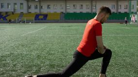 Young sportsman does workout on stadium lawn stock footage
