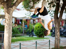Young sportsman doing front flip in the street. Young extreme athlete doing front flip between the trees. City street with outdoor cafe in background Royalty Free Stock Photography