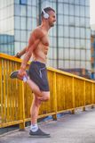 Young sportsman doing stretching exercise on the bridge. Preparing for morning training . Fitness, sport, lifestyle concept Stock Photo