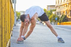 Young sportsman doing stretching exercise on the bridge. Preparing for morning training . Fitness, sport, lifestyle concept Stock Image
