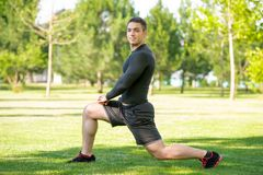 Young sportsman doing stretching exercise outdoors Royalty Free Stock Photography