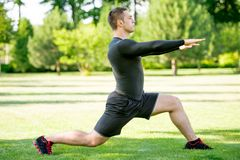 Young sportsman doing stretching exercise in the Stock Photos