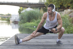 Young sportsman doing stretching exercise by the rive. R, preparing for morning training in the park. Fitness, sport, lifestyle concept& x22 Stock Image