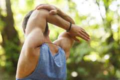 Young sportsman doing stretching exercises outdoors. In summer Royalty Free Stock Photography