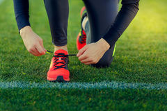 Young sportsman dresses his shoes. In training on a green football field stock images