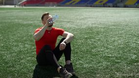 Young sportsman drinks water on a stadium lawn while rests after workout stock video