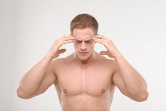 Young sportsman feeling pain. Athletic man, fitness man feeling pain in his head raising his hands to his temples isolated on white. Concept of sport, trauma stock photos