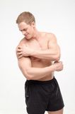 Young sportsman feeling pain. Athletic man with pain in his arm isolated on white background. Concept of sport, trauma, pain royalty free stock photos