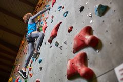 Moving upwards. Young sportsman grabbing by grips on climbing wall while moving upwards Royalty Free Stock Photography