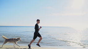 Young sportsman and his dog running along the beach slow motion stock video footage