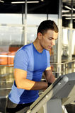 Young sportsman includes treadmill. Young man includes treadmill in sportclub Royalty Free Stock Image