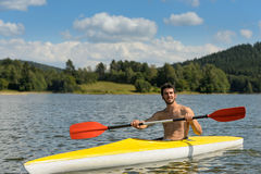 Sporty man in kayak with oar summer Stock Image