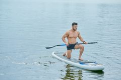 Young sportsman keeping long oar, standing on one one knee, swimming on sup board in city lake. Stock Photo