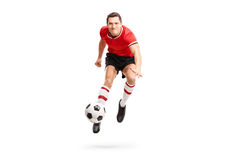 Young sportsman kicking a football in mid-air Royalty Free Stock Image