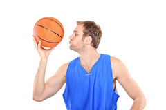Young sportsman kissing a basketball Royalty Free Stock Images