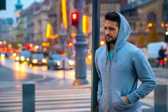 Young sportsman leaning to a pillar. A handsome young sportsman leaning to a pillar on the street with the car lights behind him royalty free stock image