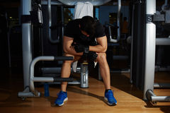 Young sportsman lower his head tired to struggle and fight with himself. Tired to working out young athlete having a rest sitting on simulator gym equipment royalty free stock image