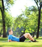 Young sportsman lying on a mat in a park Stock Images