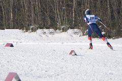 Young sportsman with number skiing in the Alps on a Sunny day-skier rides down for winter snow sports competitions- stock photography