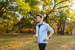 Young sportsman outdoors in park listening music with earphones running stock photos
