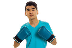 Young sportsman practicing boxing in blue gloves isolated on white background Stock Photography