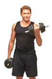 Young sportsman pumping up bicep muscles with black dumbbells. Smiling satisfied handsome young sportsman pumping up bicep muscles with black dumbbells, looking Stock Images