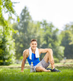 Young sportsman resting seated on grass in a park Royalty Free Stock Photos