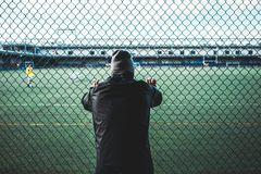 Young sportsman resting after sport excersion run near the fence. Concept. Tired runner athlete leaned and holding on to the rabitz fence. Young sportsman stock photography