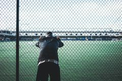 Young sportsman resting after strong and fast run near the fence. Tired athlete man leaned and holding on to the rabitz fence. Young sportsman resting after royalty free stock photo