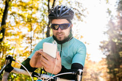 Young sportsman riding bicycle, holding smartphone, sunny autumn Stock Photos