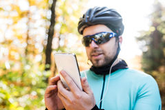 Young sportsman riding bicycle, holding smartphone, sunny autumn Stock Image
