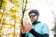 Young sportsman riding bicycle, holding smartphone, sunny autumn Stock Photography