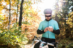 Young sportsman riding bicycle, holding smartphone, sunny autumn Royalty Free Stock Photo