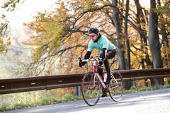 Young sportsman riding his bicycle outside in sunny autumn natur Stock Image