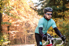 Young sportsman riding his bicycle outside in sunny autumn natur Royalty Free Stock Photos