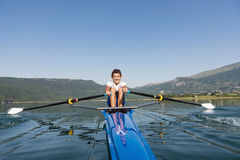 The young sportsman is rowing on the racing kayak Stock Images