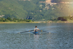 The young sportsman is rowing on the racing kayak Royalty Free Stock Photo