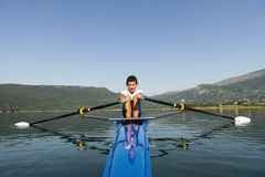 The young sportsman is rowing on the racing kayak Royalty Free Stock Image
