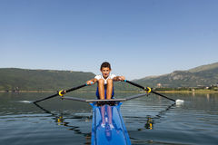 The young sportsman is rowing on the racing kayak Royalty Free Stock Photography