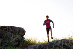 Young Sportsman Running on the Rocky Mountain Trai in the Evening. Active Lifestyle Stock Photography